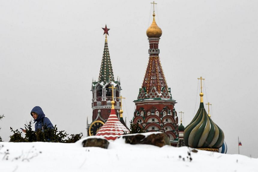 A woman walking under overcast skies in Zaryadye Park, with St Basil's Cathedral in the background, on Dec 26, 2017.