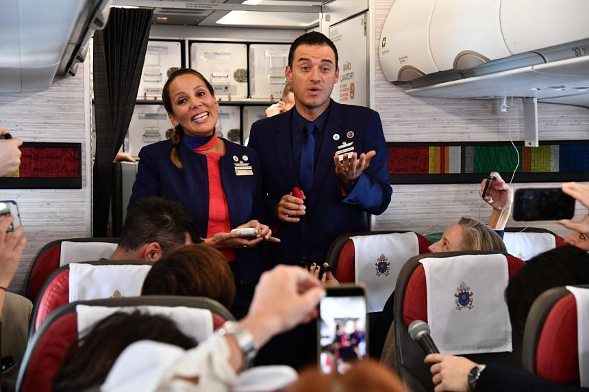 Crew members Paula Podest (L) and Carlos Ciufffardi talk to people on the plane moments after being married by Pope Francis.