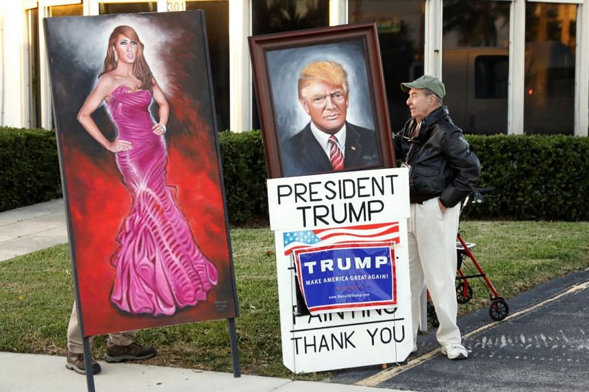 A supporter stands by paintings of US President Donald Trump and first lady Melania Trump as Trump's motorcade passes in West Palm Beach, Florida, on Dec 10, 2017.