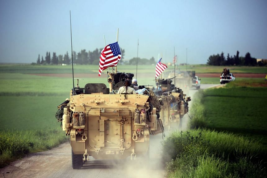 US forces, accompanied by Kurdish People's Protection Units fighters, driving their armoured vehicles near the northern Syrian village of Darbasiyah on April 28, 2017.