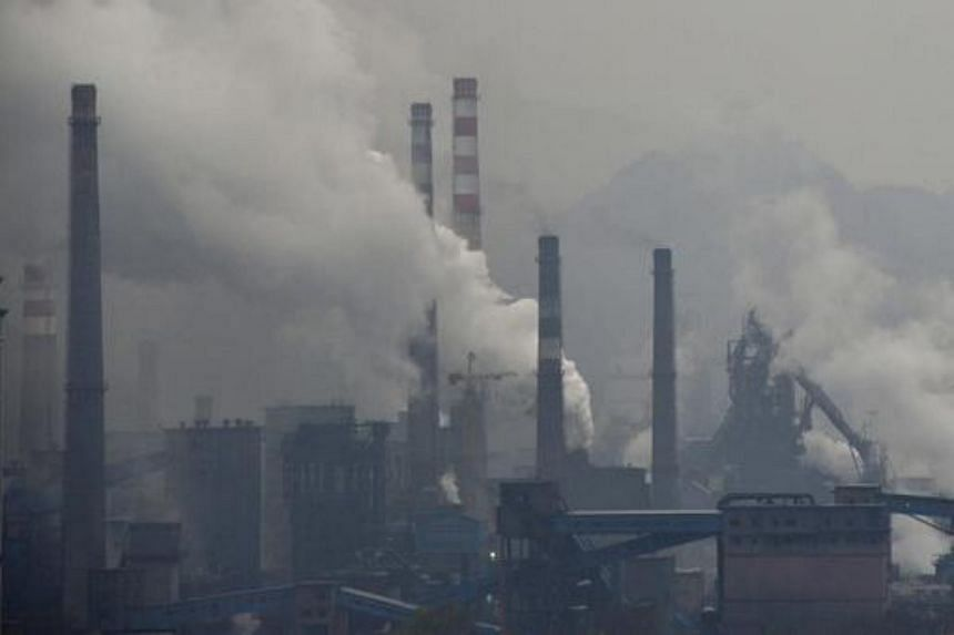 Smoke rises from chimneys and facilities of steel plants on a hazy day in China.
