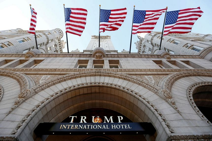 Flags fly above the entrance to the Trump International Hotel on its opening day in Washington, DC, on Sep 12, 2016.