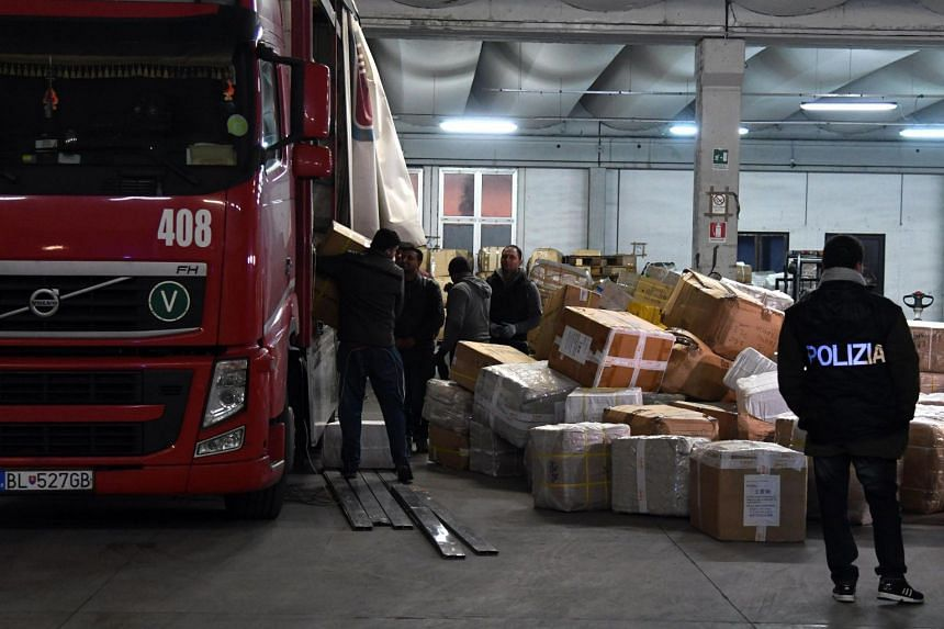 """Policemen check merchandise during a sting operation against a """"Chinese mafia organisation"""" in Prato, Italy, on Jan 18."""