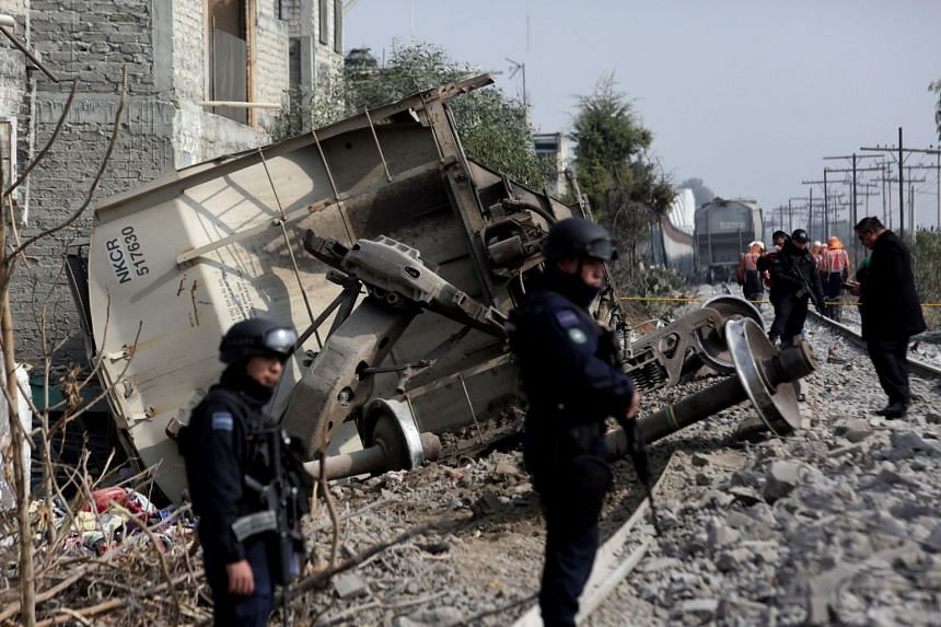 Federal police guard the site where the car of a cargo train ran off the tracks knocking a home in Ecatepec.