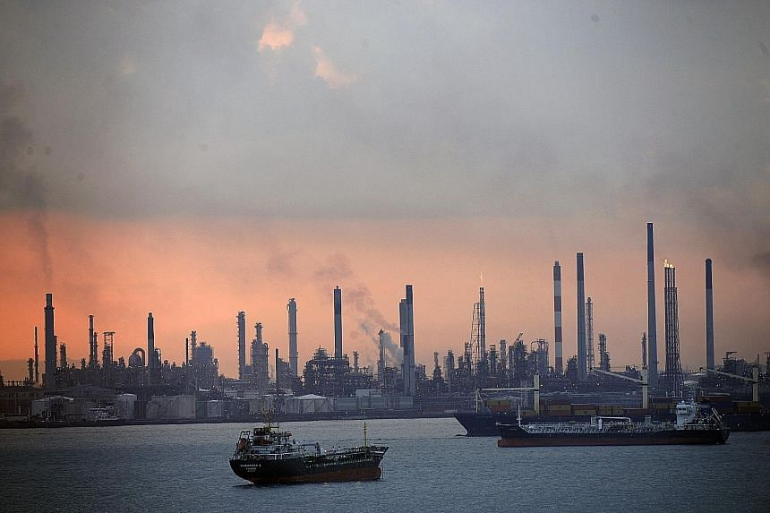 The three men were charged in connection with the theft of oil from Shell's Pulau Bukom refinery.