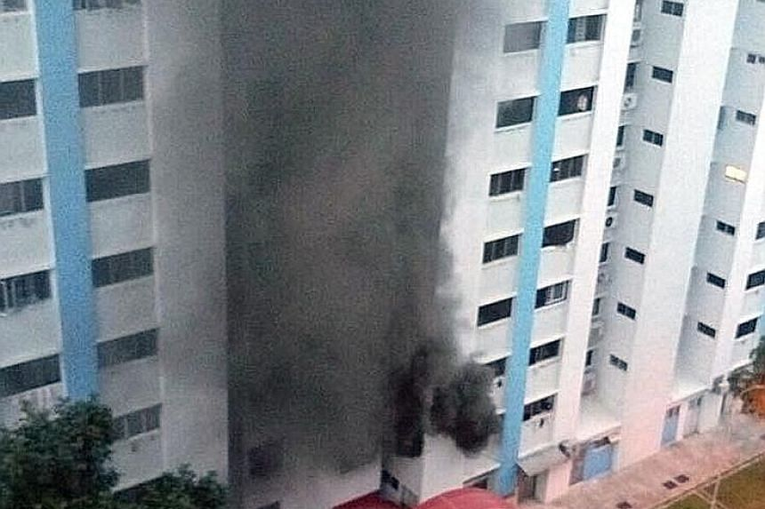 A woman in her 80s and another in her 30s were taken by ambulance to Tan Tock Seng Hospital after suffering from breathlessness. The cause of the fire in the second-floor unit (below) is being investigated. Left: The fire - seen from the front of Blo