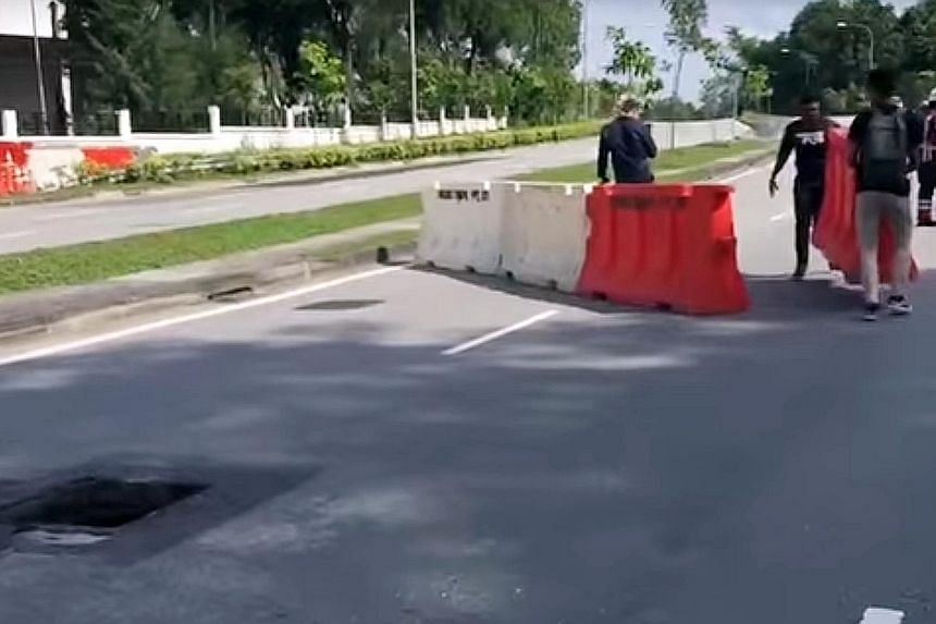 Passers-by used barricades from a construction site to channel traffic away from an exposed manhole in Jalan Bahar yesterday.