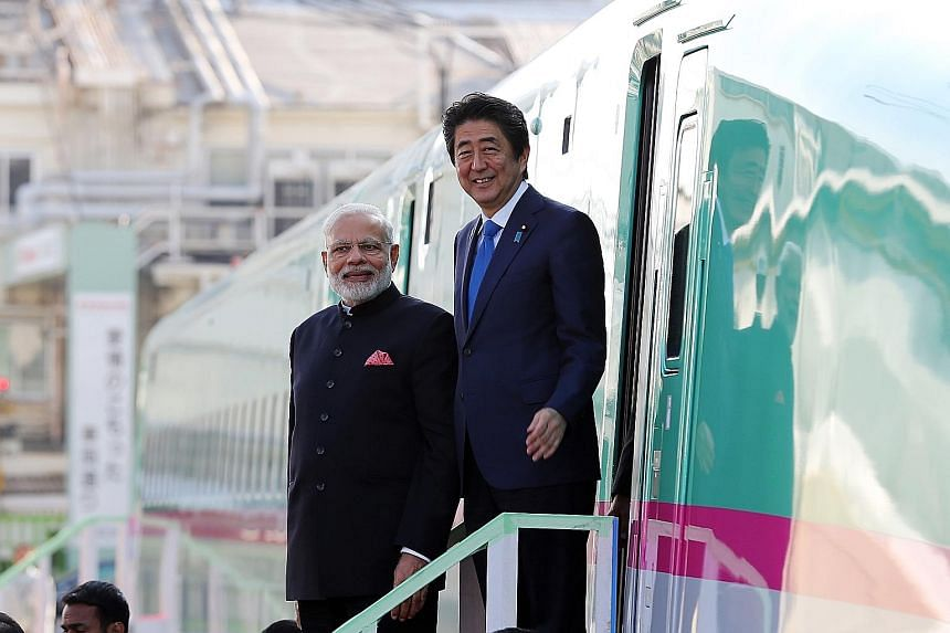 Indian Prime Minister Narendra Modi and his Japanese counterpart Shinzo Abe standing beside a Shinkansen bullet train during a 2016 visit to a Kawasaki Heavy Industries plant in Kobe, Japan.