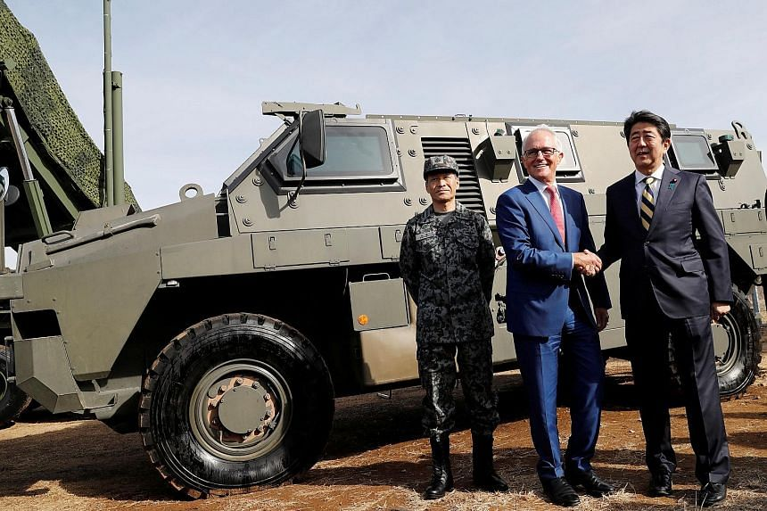 Australian Prime Minister Malcolm Turnbull with Japanese Prime Minister Shinzo Abe at the Narashino exercise field in Funabashi, east of Tokyo, yesterday. The two nations will hold a joint military exercise later this year.