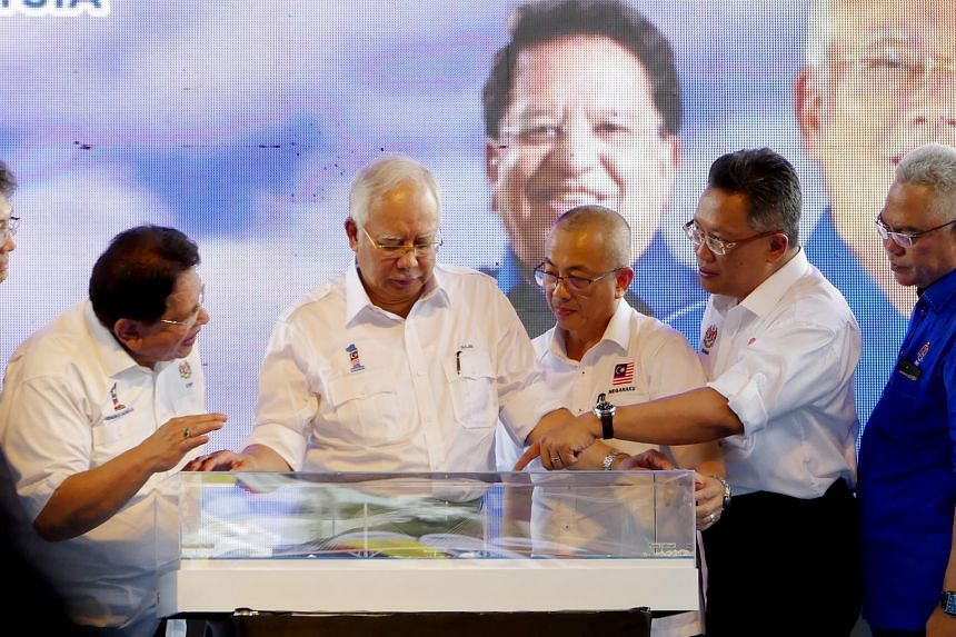 Malaysian Prime Minister Najib Razak (second from left) looking at a model of the Labuan-Sabah bridge yesterday. With him are Federal Territories Minister Tengku Adnan Tengku Mansor (far left), MP for Labuan and chairman of Labuan Corporation Rozman