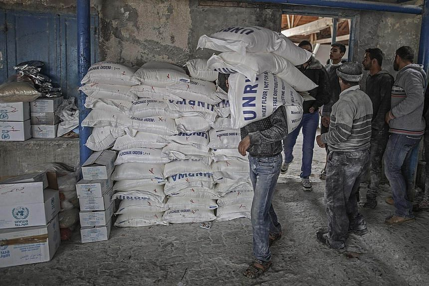 A Palestinian refugee man carries a sack of flour at the United Nation food distribution center in Al Shateaa refugee camp, in Gaza city, on Jan 15, 2018.
