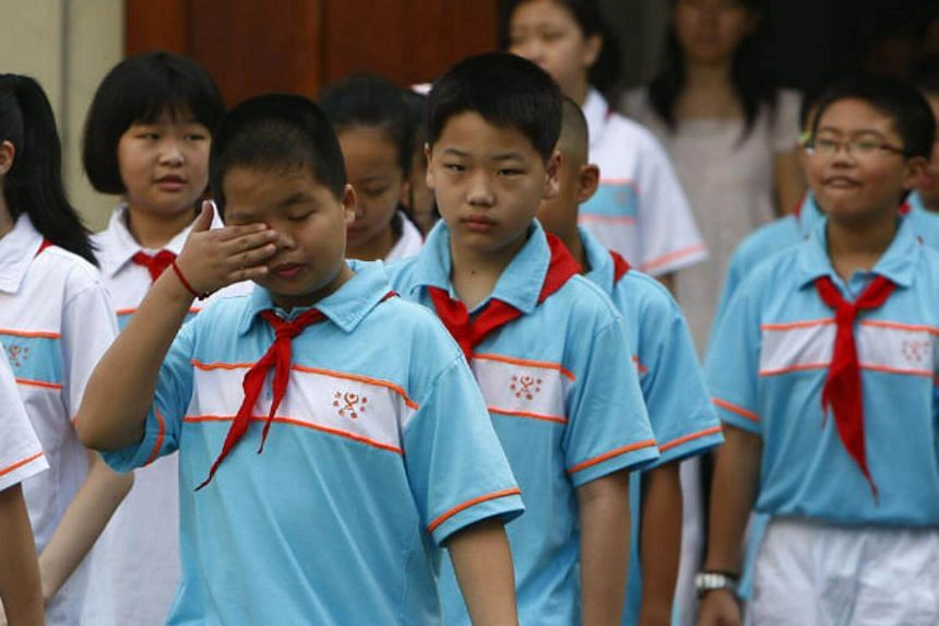 A sleepy student rubs his eyes during a ceremony held to open a new semester at Xiangming Junior High School, in Shanghai, on Sept 1, 2015.