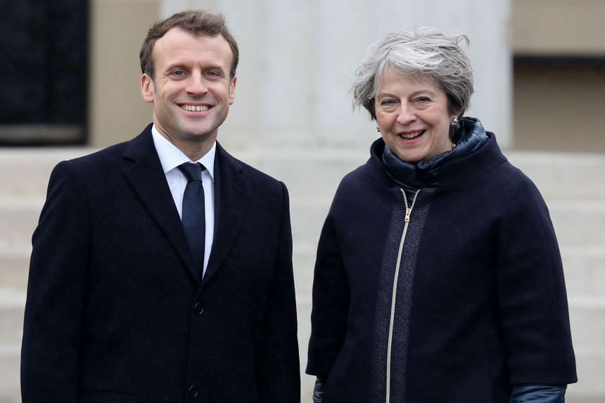 May (right) and Macron smile during a ceremony at the Royal Military Academy Sandhurst, on Jan 18, 2018.