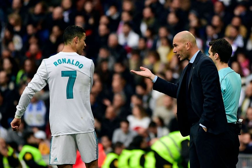 Real Madrid's coach Zinedine Zidane (right) speaks to Cristiano Ronaldo during the match between Real Madrid and Sevilla, on Dec 9, 2017.
