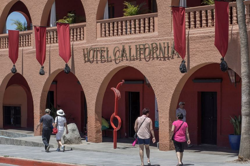 Tourists walk past Hotel California in the town of Todos Santos in Mexico on May 2, 2017.