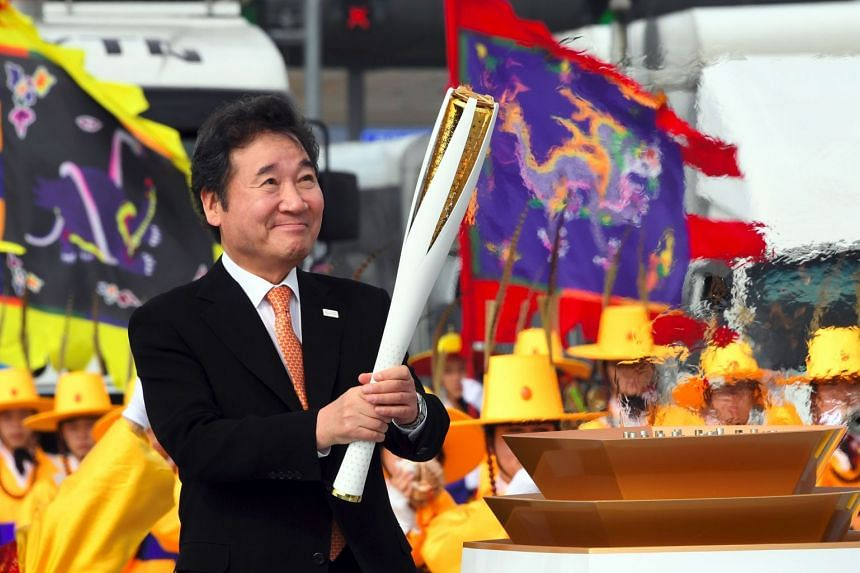 South Korean Prime Minister Lee Nak Yon lights the Olympic torch during a ceremony of the start the Olympic torch relay across South Korea on Nov 1, 2017.
