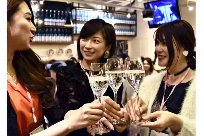 Nihonshu Joshikai group leader Aimee Ujiie (right) raises a glass of sparkling sake with attendees of a sake-themed event in Tokyo.