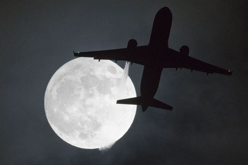 A plane flies in front of a supermoon on its approach to London's Heathrow Airport on Jan 1, 2018.