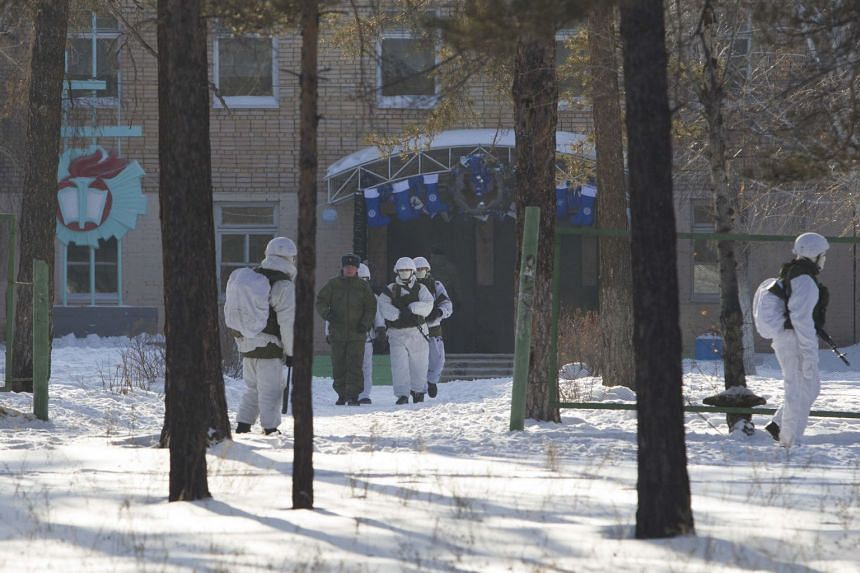 Law enforcement officers gather near a school after a student with an axe attacked schoolchildren and a teacher in Ulan-Ude, Russia, on Jan 19.