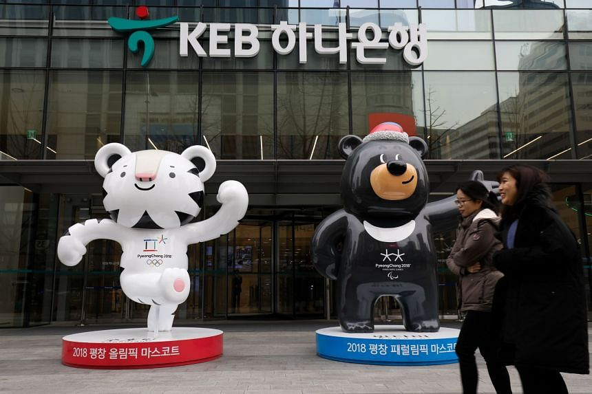 Pedestrians walk past models of the 2018 PyeongChang Winter Olympic Games mascots in Seoul.