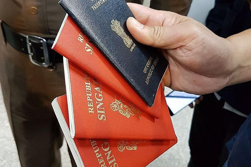 Thai immigration police showing fake Singapore and Indian passports seized from Mohammed Iqbal, who was arrested on Sunday.