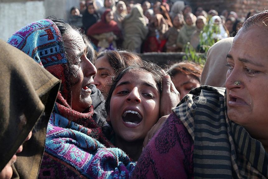 Relatives mourning near the body of Sahil Kumar, who was killed by mortar shells allegedly fired from the Pakistani side of the disputed Kashmir border in the village of Ranbir Singh Pura, about 25km from Jammu, the winter capital of Kashmir, India,