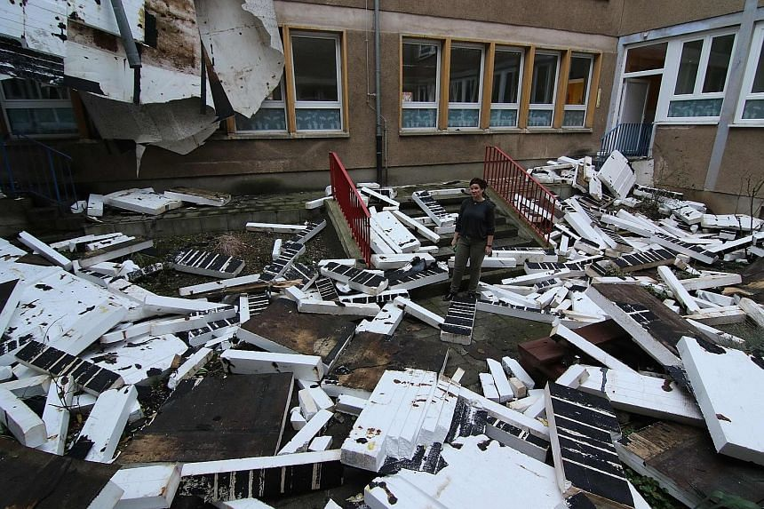Pieces of a primary school's roof littered the schoolyard yesterday in Halberstadt, eastern Germany, one day after the region was hit by Storm Friederike. A car is crushed by a large tree in Dortmund, Germany, on Thursday when gale-force winds from S