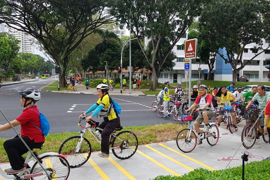 Cyclists riding on the newly opened cycling network at Bedok North Street 1, along Heartbeat@Bedok. The new dotted red lines signify a shared walking and cycling path.