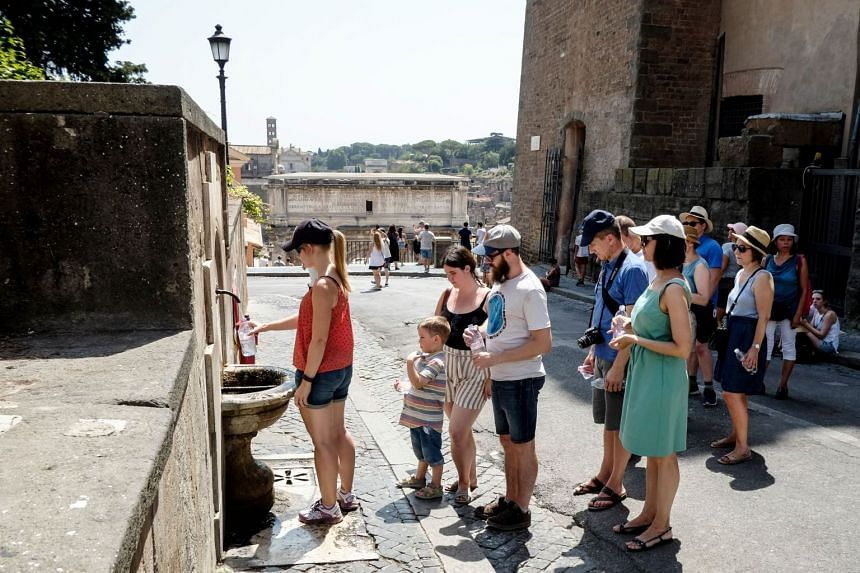 """A woman fills a bottle with water from a """"Nasone"""" (big nose), a typical Roman fountain, in front of the Foro Romano in central Rome on Aug 5, 2017, as temperatures reached more than 40 deg C."""