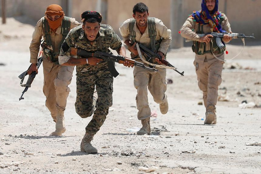 Kurdish fighters from the Kurdish People's Protection Units run across a street in Raqqa, Syria, on July 3, 2017.