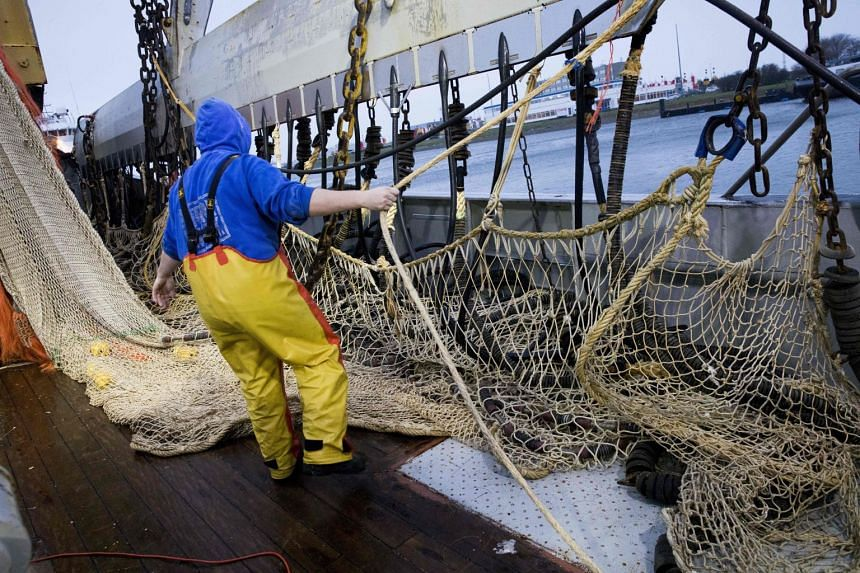 A fisherman on a Dutch fishing boat preparing electric pulse nets during departure from the harbour of Den Helder, The Netherlands, on Jan 18, 2018.