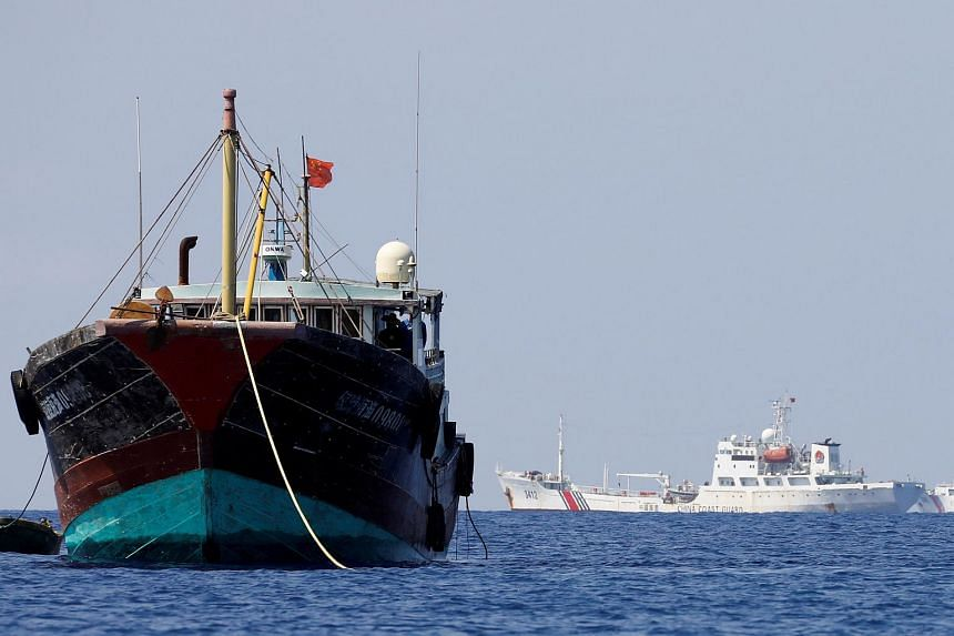 China Coast Guard vessels patrol past a Chinese fishing vessel at the disputed Scarborough Shoal, also known as Huangyan Island, on April 5, 2017.