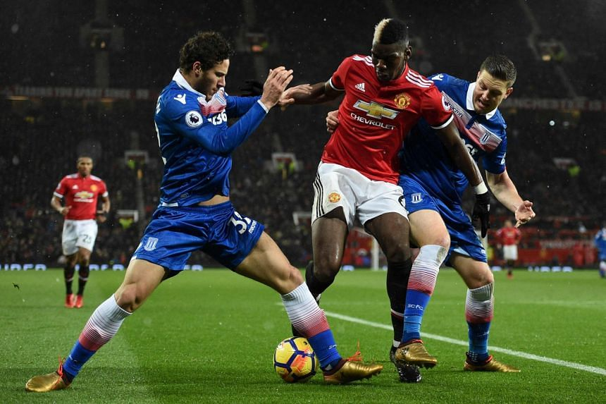 Manchester United's midfielder Paul Pogba (centre) tangles with Stoke City's Ramadan Sobhi (left) and defender Kevin Wimmer.