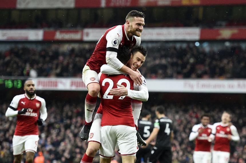 Arsenal's Laurent Koscielny (centre, right) celebrates with team mate Shkodran Mustafi (top) after scoring.