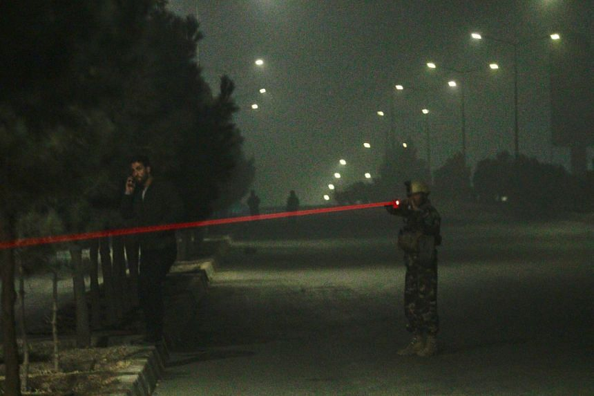 Afghan security officials take up positions near the scene of attack.