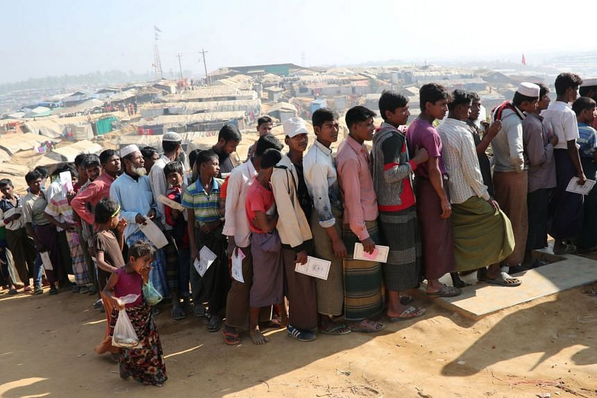 Rohingya refugees stand in a queue to collect aid supplies in Kutupalong refugee camp in Cox's Bazar, Bangladesh, on Jan 21, 2018.