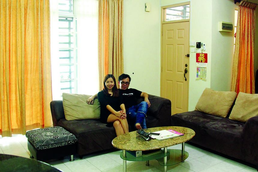 """Ms Tan and Mr Ling in the living room of their 2,540 sq ft double-storey terraced house in Johor Baru's Tebrau area. She says it is """"easy for my hubby and I to commute to Singapore for work"""" from their home."""
