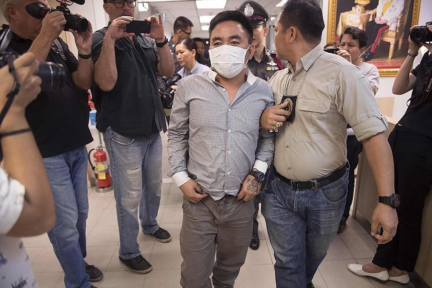 Boonchai Bach being escorted past journalists at a Bangkok police station yesterday.
