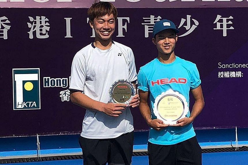 Ethan Lye (right) with his silverware for winning his second International Tennis Federation Junior title in Hong Kong yesterday. The 16-year-old overcame Chinese Taipei's Tsai Chang-lin (left) 7-5, 6-2 at the Victoria Park Tennis Court.