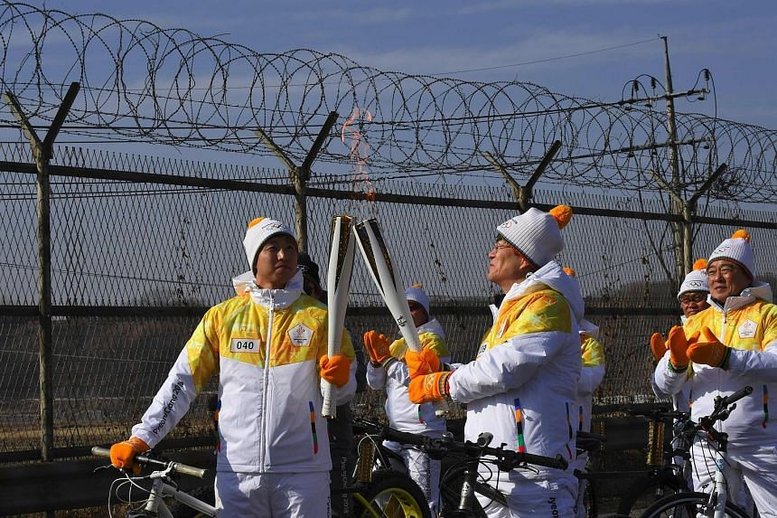 (Left) The Olympic flame is passed on the road to the border truce village of Panmunjom last Friday. (Above) IOC president Thomas Bach flanked by sports ministers Kim Il Guk (left) from North Korea and Do Jong Hwan from South Korea, at the IOC headqu