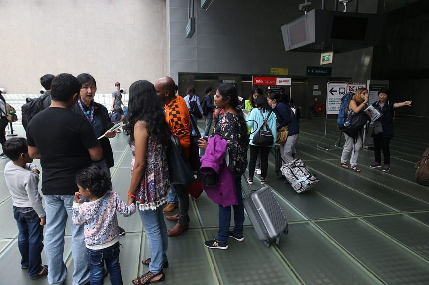LTA and SMRT staff directing members of the public at Changi Airport Terminal 2 to the shuttle bus service at Terminal 3.
