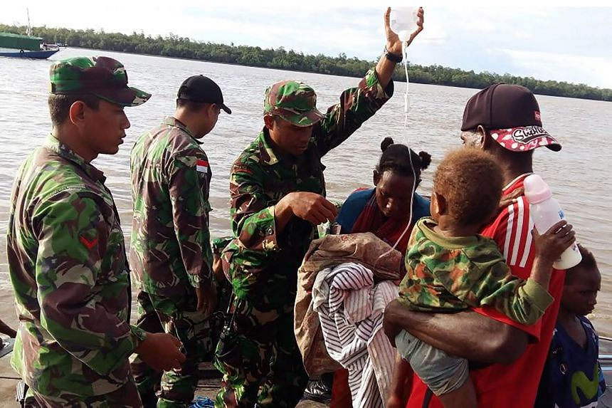 Indonesian military personnel tending to children suffering from malnutrition in Asmat, Papua Province, on Jan 20, 2018.