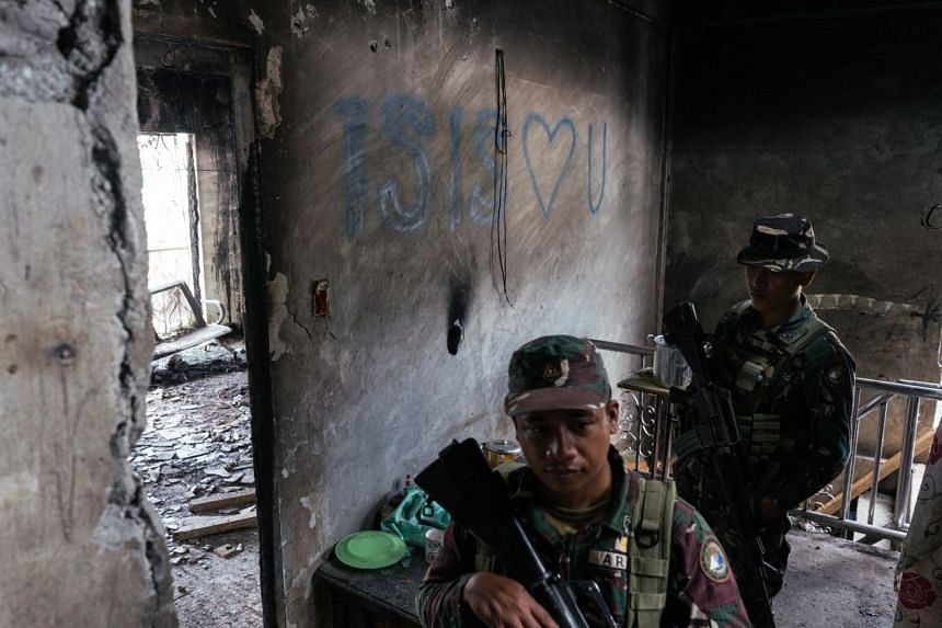 Filipino soldiers patrol a building in Marawi with pro-Islamic State graffiti on a wall in December 2017.