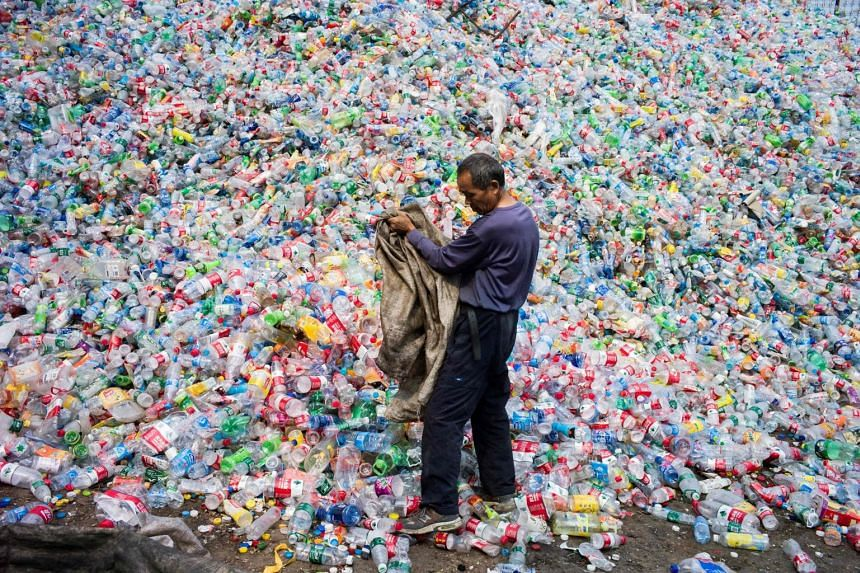 A Chinese labourer sorting out plastic bottles for recycling in Dong Xiao Kou village, on the outskirts of Beijing on Sept 17, 2015.