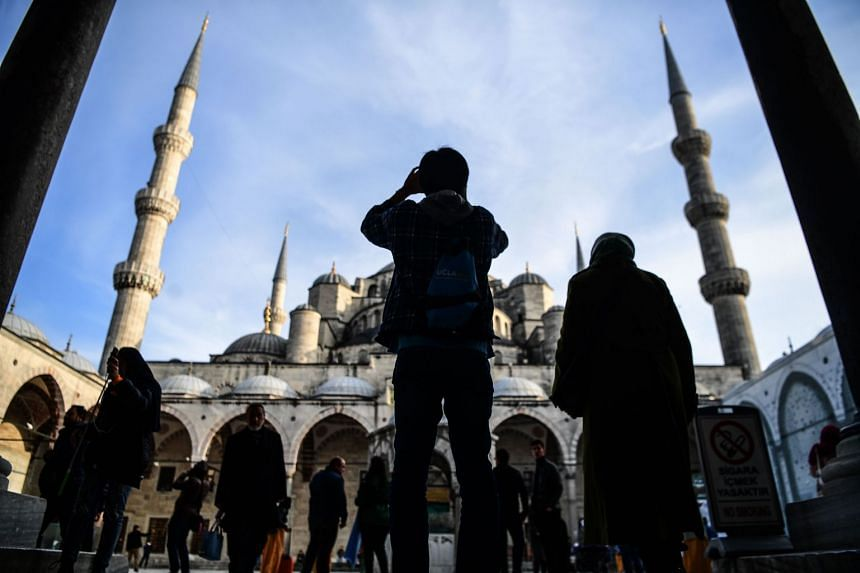 A tourist takes a picture of the Blue Mosque, also known as Sultanahmet, in Istanbul on Jan 8, 2018.