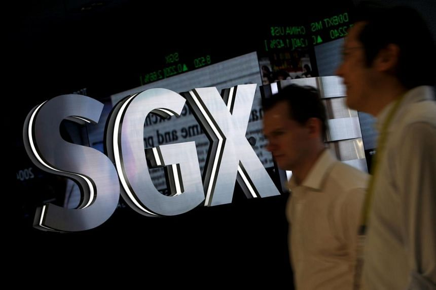 People walk past a Singapore Exchange logo at their head office in Singapore.