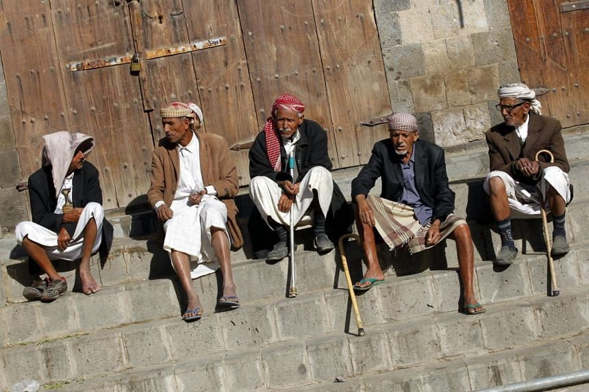 Yemenis expose themselves to the sun light to keep them warm at a market in the old city of Sana'a, Yemen.