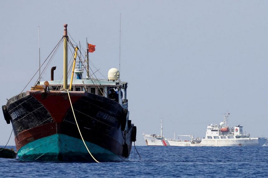 China Coast Guard vessels patrol going past a Chinese fishing vessel at the disputed Scarborough Shoal on April 5, 2017.