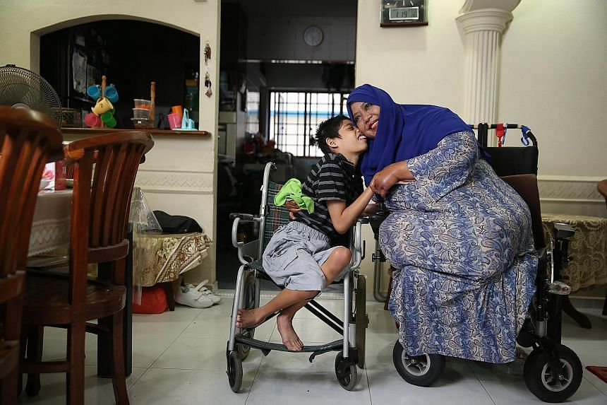 Madam Zainon Arshad with her son Huzairul Izwan. Madam Zainon lost both her legs because of diabetes. Rather than rely on her husband's income, she took up courses to learn how to make baked goods and now sells them from home, and sometimes at bazaar