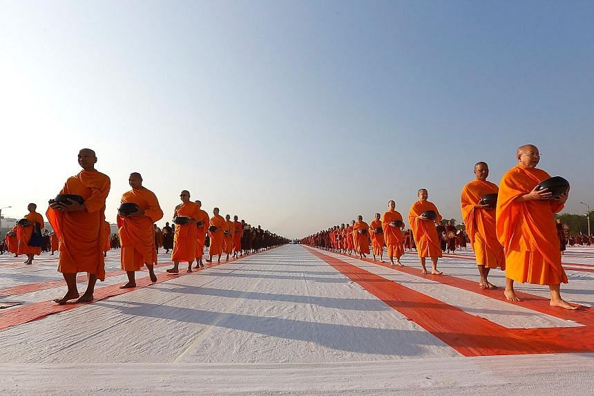 Thousands of Buddhist monks participating in an alms-offering ceremony on the runway of an abandoned airport in central Mandalay yesterday. The event in Myanmar's second-largest city was partly organised by the scandal-hit Dhammakaya temple, Thailand